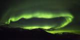 Polarlichter (Aurora borealis) über Fjord in der Region Troms, Norwegen