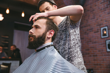 Young barber cutting hair of  bearded hipster in barbershop
