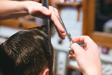 Barbers hands making haircut to man using comb and scissors