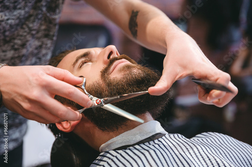 Poster, Tablou Hairdresser doing haircut of beard to young attractive man