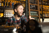 Man barista preparing coffee for his customers while laughing