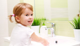 Fototapety child little girl washes her hands in bathroom