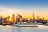New York City skyline at sunrise, as viewed from Weehawken, along the 42nd street canyon. A large cruise ship sails Hudson river, while sun beams burst between the skyscrapers. - 96731894