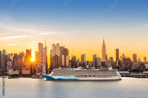 Zdjęcia na płótnie, fototapety na wymiar, obrazy na ścianę : New York City skyline at sunrise, as viewed from Weehawken, along the 42nd street canyon. A large cruise ship sails Hudson river, while sun beams burst between the skyscrapers.