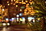 Fototapety Branch of decorated Christmas tree in late evening on the street with night illumination