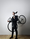 Fototapety Portrait of a handsome middle aged man wearing suit and holding his classic bicycle on the shoulder. Vertical