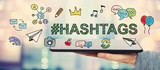 Fototapety Hashtags concept with man holding a tablet
