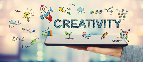 Creativity concept with man holding a tablet © Tierney
