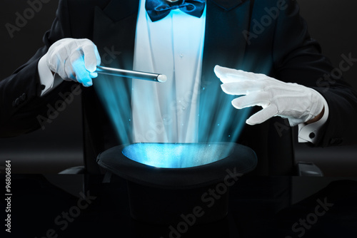 Magician Holding Magic Wand Over Illuminated Hat Poster