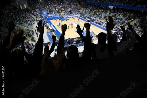 A group of spectator at a professional basketball game cheers at their team