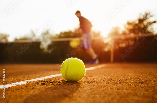 Tennis ball and silhouette of player on a clay court Tablou Canvas
