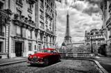 Artystyczne Paryż, Francja. Wieża Eiffla widziana z ulicy z czerwonym samochodem retro limuzyny.