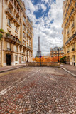 Eiffel Tower seen from the street in Paris, France.  Cobblestone pavement