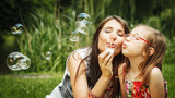 Mother and little girl blowing soap bubbles in park. - 96860059