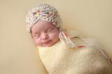 Smiling Newborn Baby Girl Swaddled in Yellow