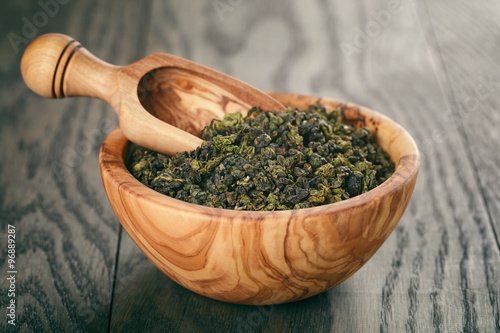 Poster oolong green tea in wood bowl on oak table