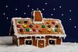 Pepparkakshus med stjärnhimmel i vinterlandskap
