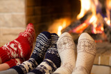 Fototapety Feet in wool socks near fireplace in winter time