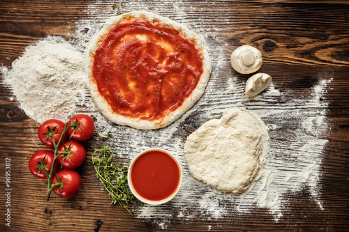 Pizza dough with ingredients on wood плакат
