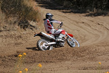 Fototapety MX rider on a motorcycle rides cornering along the sandy furrow motocross track