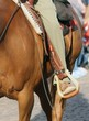 Obrazy na płótnie, fototapety, zdjęcia, fotoobrazy drukowane : Cowboy foot in the stirrup of the horse during the ride