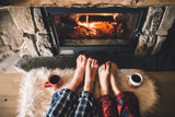 Fototapety Bare couple feet by the cozy fireplace. Man and Woman relaxes by warm fire with a cup of hot drink and warming up her feet. Close up on feet. Winter and Christmas holidays concept