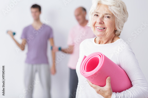 Happy elderly woman at gym