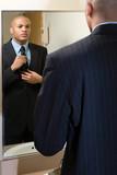 Fototapety Man adjusting his tie in mirror