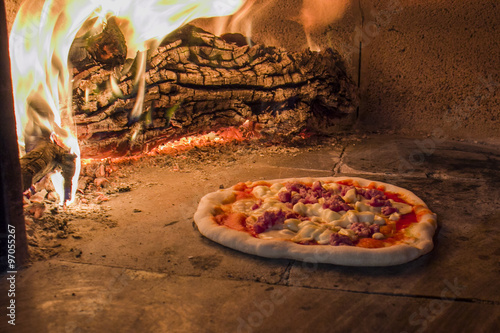 Pizza with smoked cheese and sausage in a traditional wood oven