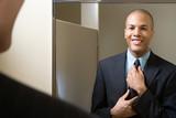Fototapety Man adjusting tie in mirror