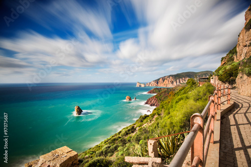Foto op Plexiglas Cyprus Walkway along the Mediterranean coast with rough sea and blue sky in long exposure