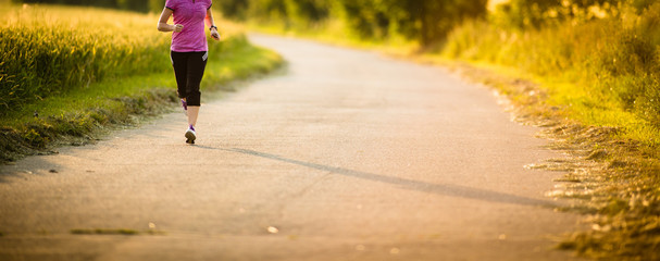 Detail of legs of a female runner on road - jog workout/well-bei