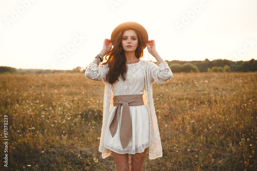 Poster Fashion portrait of beautiful young pretty girl with hippie outfit holding hat outdoors at sunset