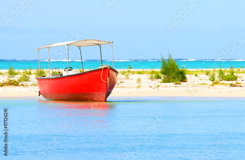 Red motor boat on Indian Ocean near Ile Aux Cerfs Island ( Mauritius Island). Blue sea and beach in tropical paradise. - 97126241