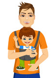 father holding little boy with baby carrier