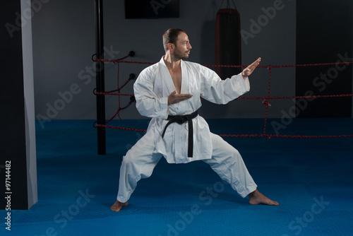Fototapeta Man In White Kimono And Black Belt Training Karate