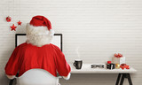Santa Claus responds to letters on a computer for Christmas