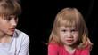 Постер, плакат: Две сестры Сильный злой взгляд маленького ребенка Старшая сестра смотрит на младшую Черный фон