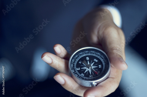Businessman with a compass holding in hand, color tone film look плакат