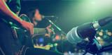 Gitarzysta na scenie z mikrofonem na tle, miękkie i rozmycie koncepcji
