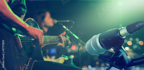 Guitarist on stage with microphone for background, soft and blur concept Poster