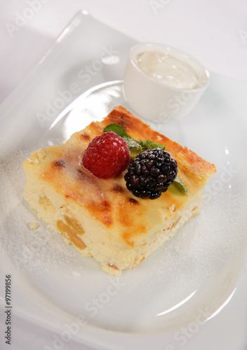 """Baked pudding for breakfast with fresh berries and sour cream"""" Stock ..."""