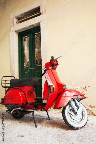 Foto op Canvas Scooter Red scooter on a city street