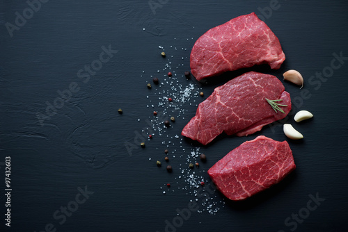 Fresh black angus beefsteaks, black wooden background, copyspace Poster