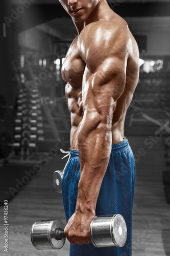 obraz lub plakat Muscular man posing in gym, showing triceps. Strong male naked torso abs, working out, focus on the hand