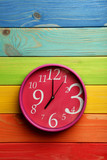 Pink round clock on a colorful wooden table