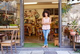 Woman standing happily in the entrance of her coffee shop - 97463421