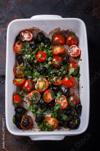 fish in a ceramic form with black olives,tomatoes,lemons and herbs ...