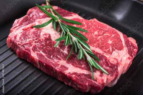 Raw marbled meat steak Ribeye on grill pan on dark wooden background Poster