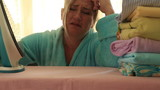 Depressed, tired housewife ironing clothes